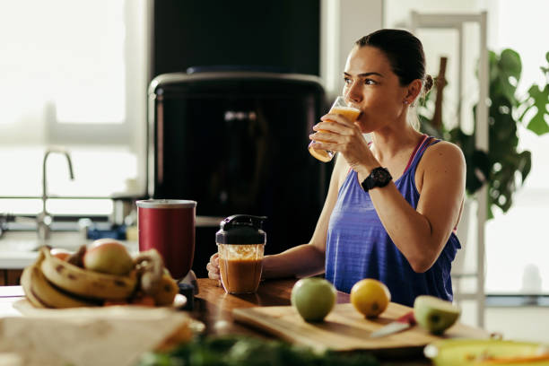 Young athletic woman drinking fruit smoothie in the kitchen. stock photo