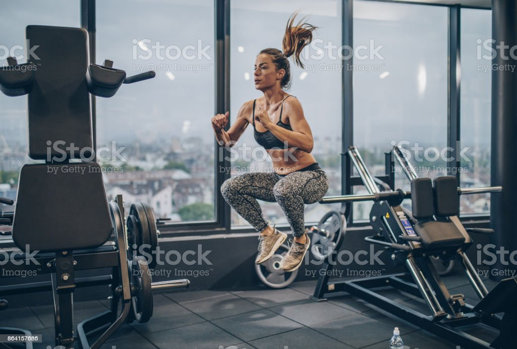 Young athletic woman exercising jumps in a health club. royalty-free stock photo