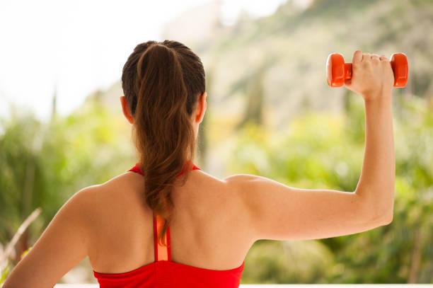 junge sportliche frau ausübung auf veranda: überkopfdrücken für kraft im oberkörper - schmale schulter stock-fotos und bilder