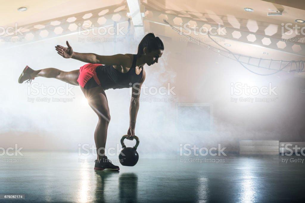 Junge sportliche Frau mit Wasserkocher Glocke in einem Fitnessstudio trainieren. - Lizenzfrei Aktiver Lebensstil Stock-Foto