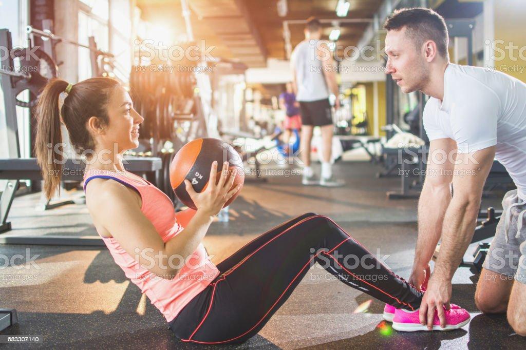 Young athletic woman having pilates training with fitness instructor.; royaltyfri bildbanksbilder