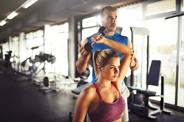 young athletic woman having weight training with fitness instructor. - entrenador personal fotografías e imágenes de stock