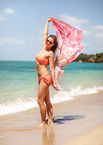 1155046257 istock photo Young athletic woman in bikini and sunglasses holding scarf that is waving behind her in wind, calm sea in background. 1178944493