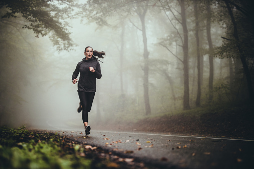 Young athletic woman jogging on the road in foggy forest.