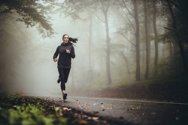 Young athletic woman jogging on the road in foggy forest. Determined athletic woman running through misty nature. Copy space. running stock pictures, royalty-free photos & images