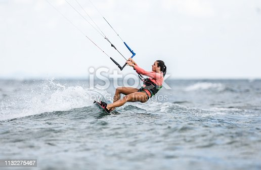 Young woman enjoying in kiteboarding during summer day at sea. Copy space.