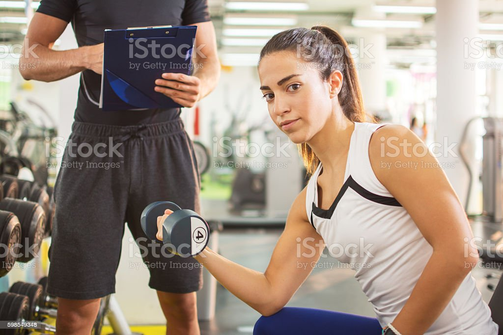 Young athletic woman lifting weights in gym. stock photo