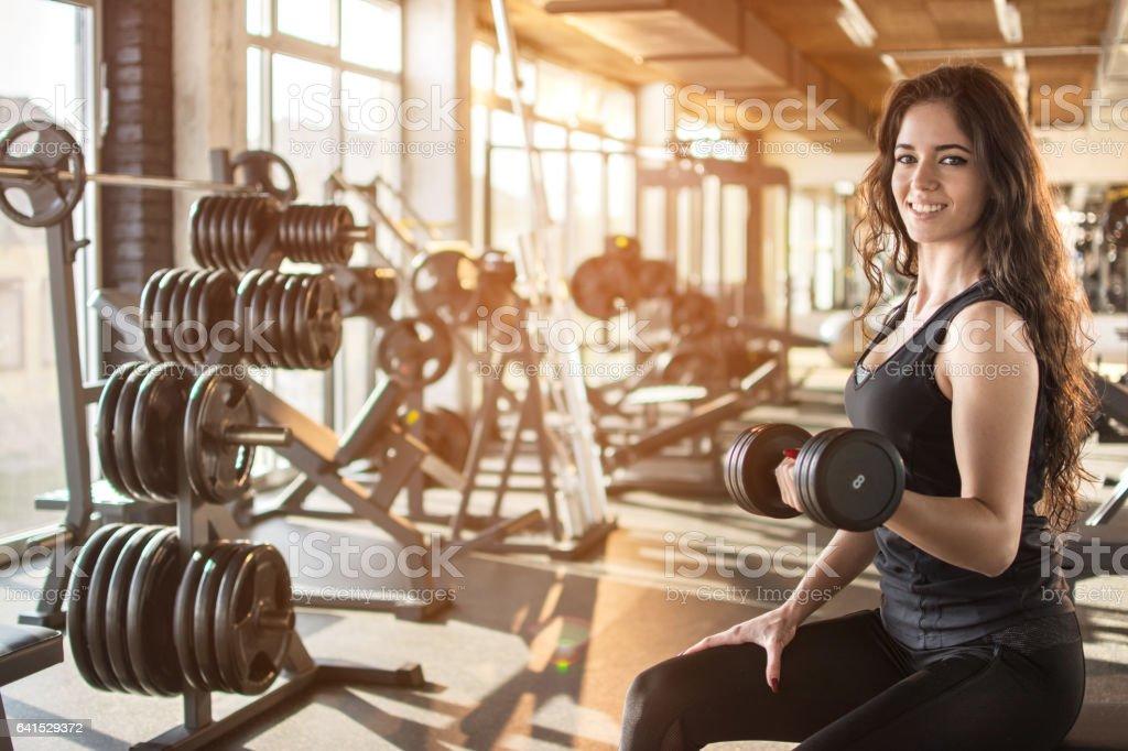 Joven atlética bombeo de los músculos con pesas. - foto de stock