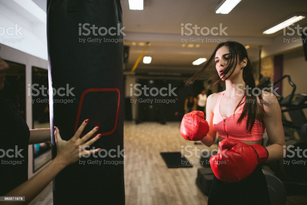 Young athletic woman punching a bag on a boxing training stock photo