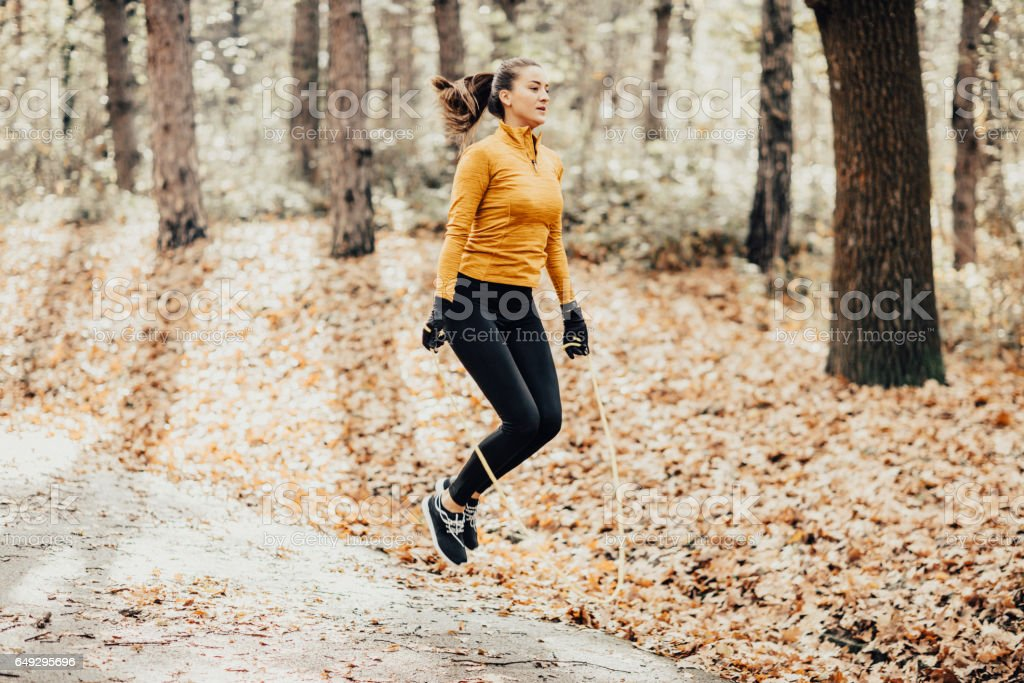 Young athletic woman skipping rope in the park stock photo