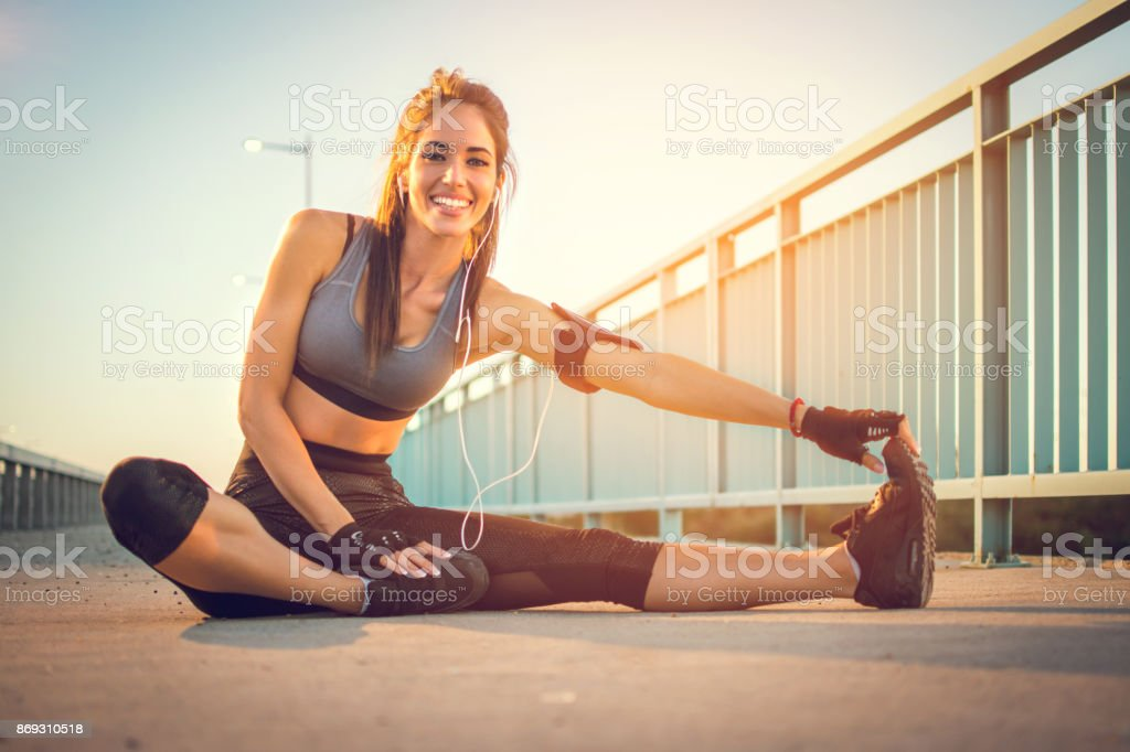 Young athletic woman warming up on a road at sunset. stock photo