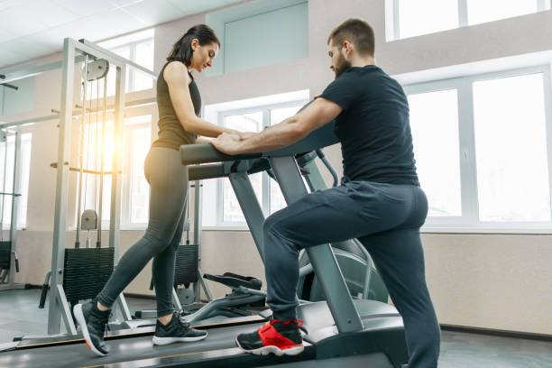young athletic women on treadmill, personal instructor coaching and helping client woman. fitness, sport, training, people concept. - runner rehab gym foto e immagini stock