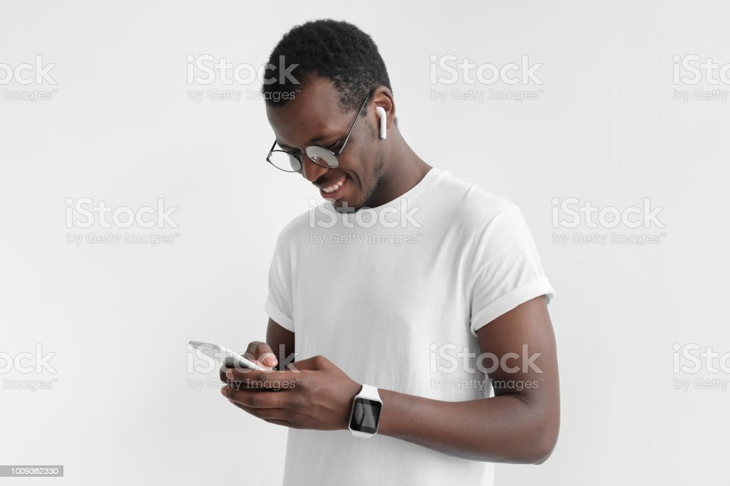 Young attractive african american dark skin man looking and at smartphone with  while texting, using mobile phone, isolated on gray background stock photo