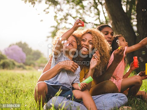 518064982 istock photo Young attractive african american family blowing bubbles in the 513584326