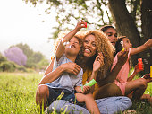 Young african-american family sharing a special moment in the sun blowing colouful soap bubbles and laughing toghether cheerfully.