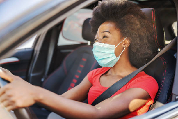 Young attractive african woman with mask on her face driving her car during covid-19 pandemic. stock photo