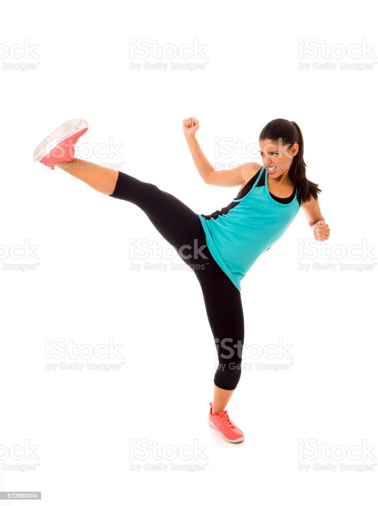 young attractive and furious latin sport woman in fight and kick boxing training workout throwing aggressive kick attack isolated on white background stock photo