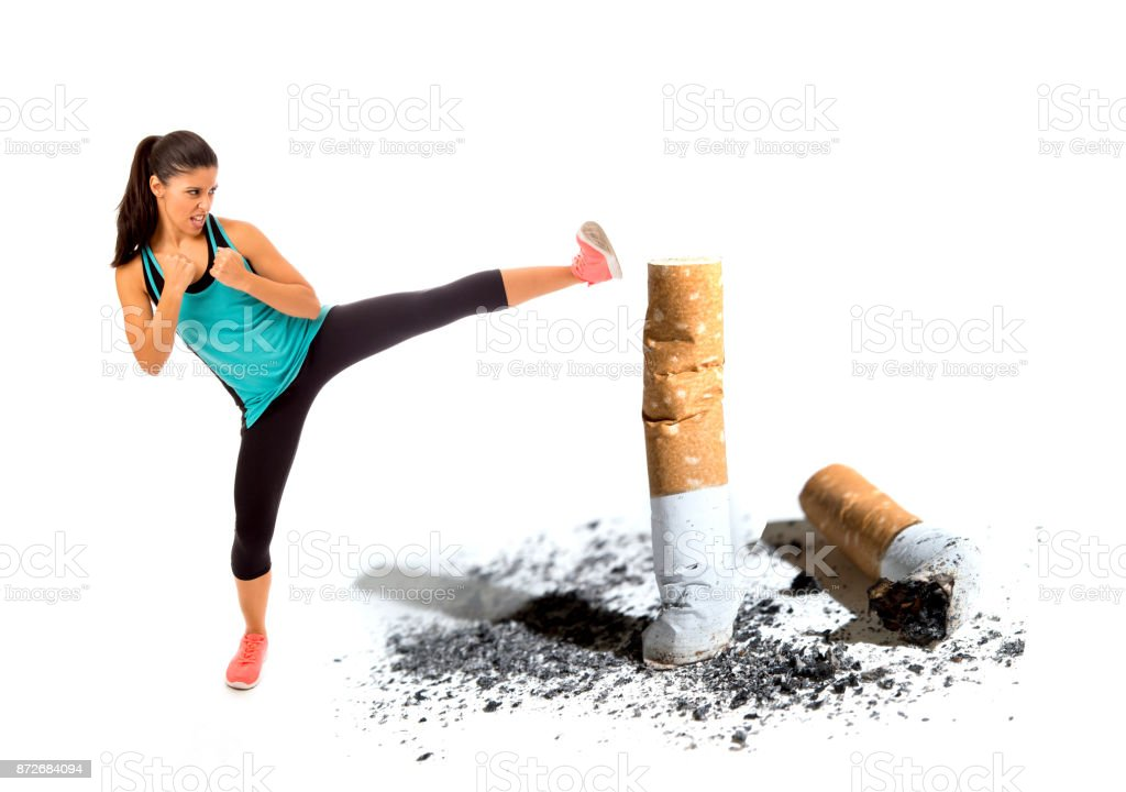 young attractive and furious latin sport woman in fight combat kick attacking angry against cigarette butt in stop and anti smoking advertising campaign stock photo