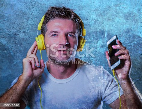 istock young attractive and happy cool man listening to music song with yellow headphones using internet mobile phone dancing in trance singing groovy and excited isolated on grey background 973274518