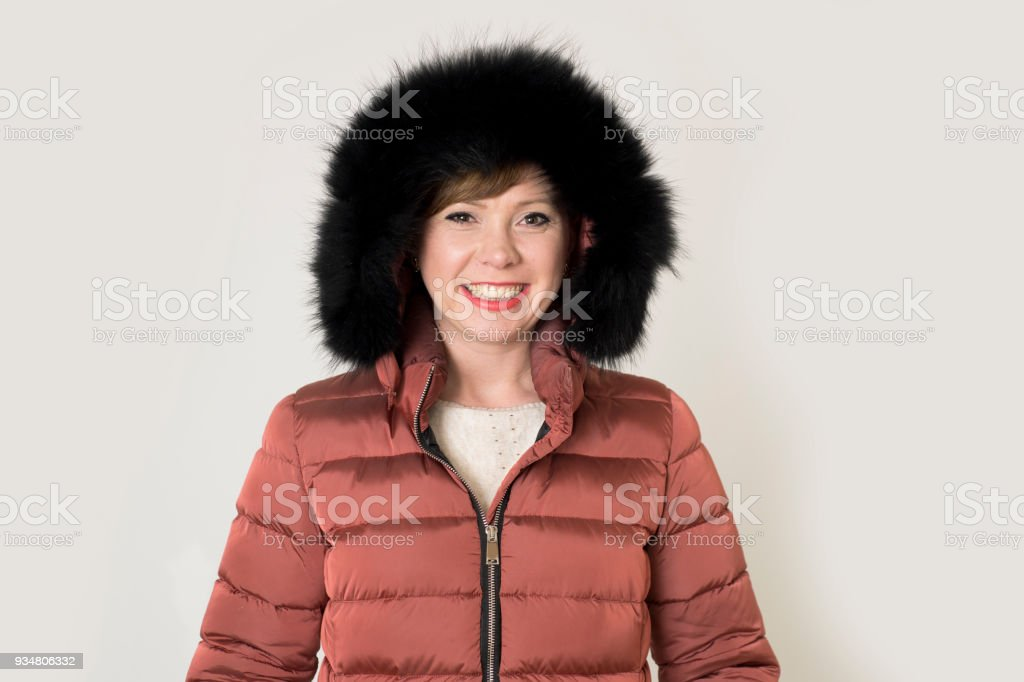 매력적이 고 행복 한 계절 패션에 회색 배경에 빨간 머리 백인 여자 그녀의 20 대 또는 30 대 밝고 웃는 입고 따뜻한 겨울 재킷 및 모피 후드 포즈에 절연 영 - 로열티 프리 20-29세 스톡 사진