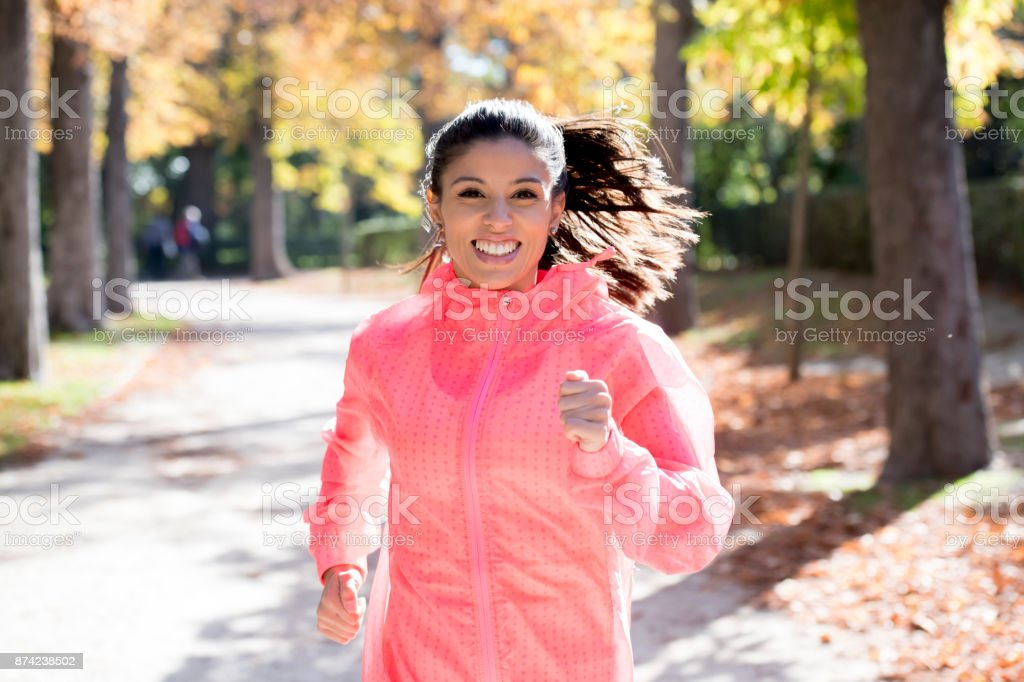young attractive and happy runner woman in Autumn sportswear running and training on jogging outdoors workout in city park with trees and yellow leaves stock photo