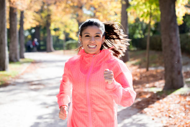 junge attraktive und glücklich Läufer Frau Herbst Sportswear running und training auf Joggen im Freien Training im Stadtpark mit Bäumen und gelbe Blätter – Foto