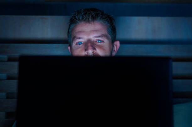 attraktiv und entspannt internet-süchtigen jüngling vernetzung konzentrierte sich spät in der nacht im bett mit laptop-computer in social-media-sucht oder workaholic geschäftsmann-konzept - sex sexuelle themen stock-fotos und bilder