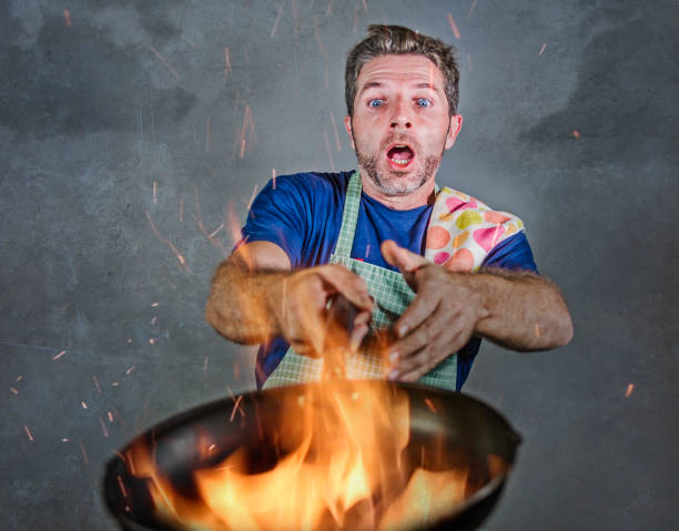 young attractive and shocked messy home cook man with apron holding pan in fire burning the food in kitchen disaster and unskilled and unexperienced terrible home cook at domestic cooking - fail cooking imagens e fotografias de stock