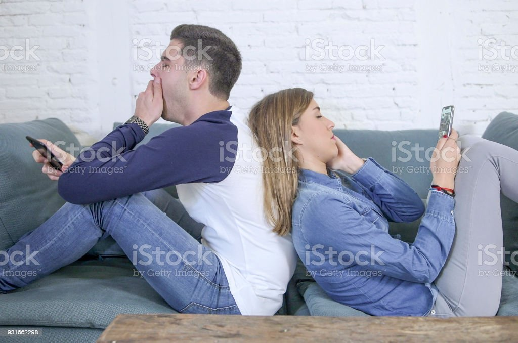 young attractive and tired internet addict couple using app on mobile phone ignoring each other sitting back to back at home living room sofa couch in slaves to smart phone concept stock photo