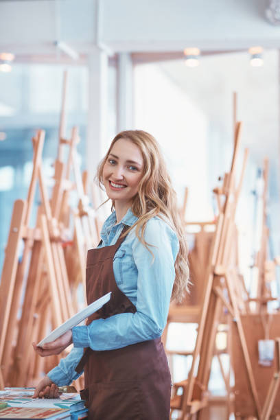 Young attractive artist in the art store stock photo