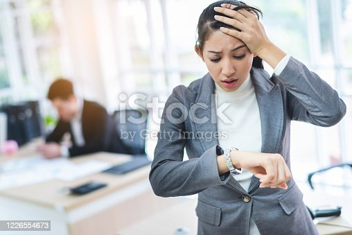 istock Young attractive Asian business woman looking at the watch time worried and afraid of getting late to meeting with boss or customer. 1226554673