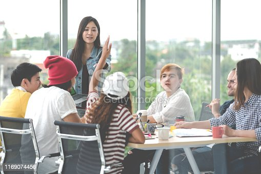 istock Young attractive asian creative hipster female leader standing at modern office happy talking and brainstorming idea presentation with teamwork. Casual asian people business meeting workshop concept. 1169074456
