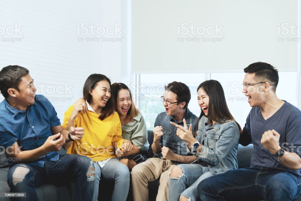 Young Attractive asian group of friends talking and laughing with happy in gathering meeting sitting at home feeling cheerful and enjoy game in leisure time together. People in blue or yellow wearing. stock photo