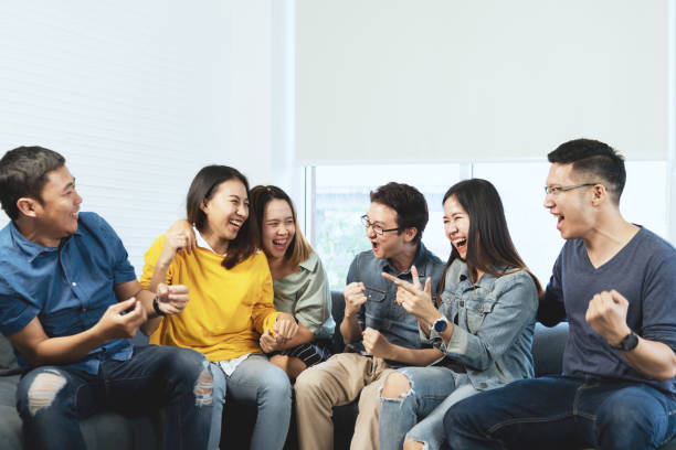 young attractive asian group of friends talking and laughing with happy in gathering meeting sitting at home feeling cheerful and enjoy game in leisure time together. people in blue or yellow wearing. - политическая партия стоковые фото и изображения