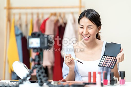 Young attractive asian woman beauty blogger or vlogger smiling looking at camera and talking on video shooting while make up. Social media young asian micro influencer in relax casual style at home.