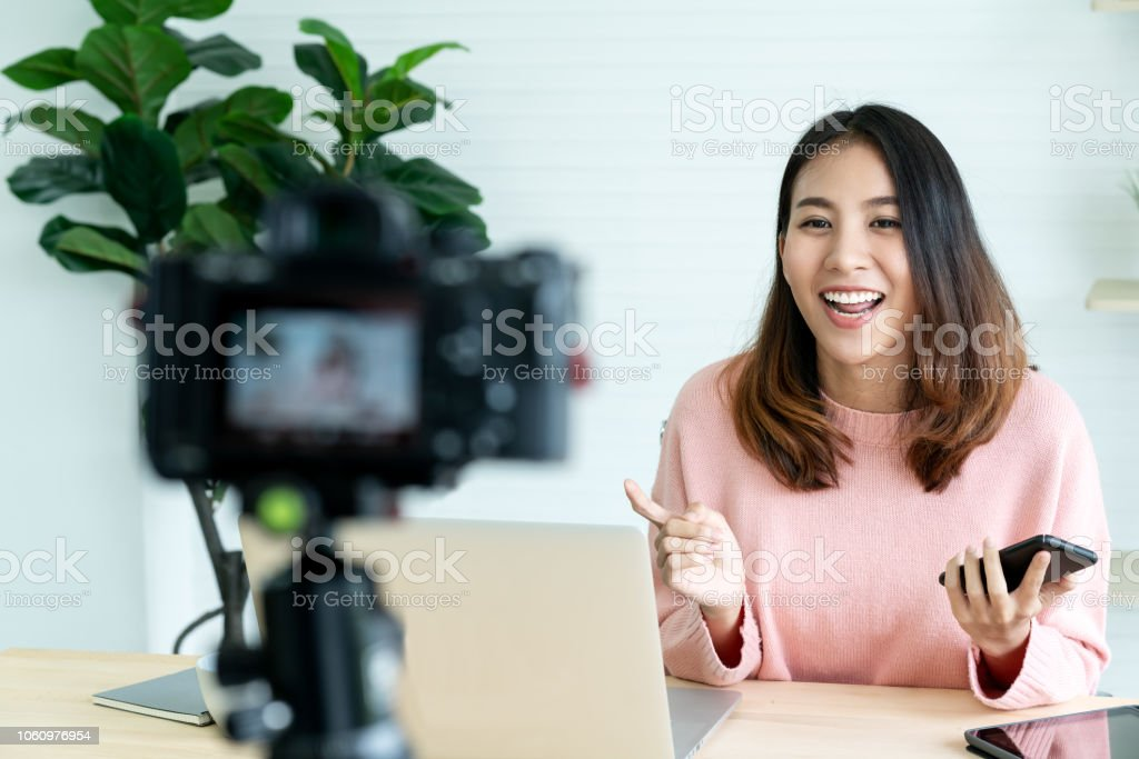 Young attractive asian woman blogger or vlogger looking at camera and talking on video shooting with technology. Social media influencer people or content maker concept in relax casual style at home. - Zbiór zdjęć royalty-free (Azja)