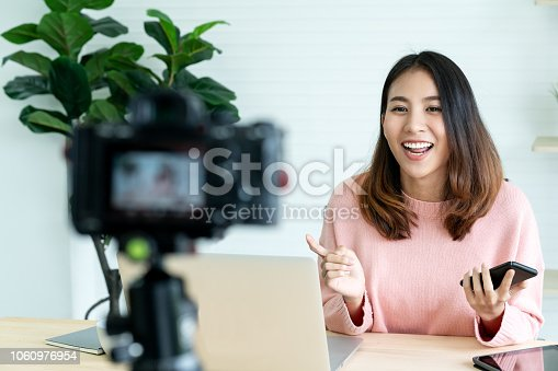 istock Young attractive asian woman blogger or vlogger looking at camera and talking on video shooting with technology. Social media influencer people or content maker concept in relax casual style at home. 1060976954