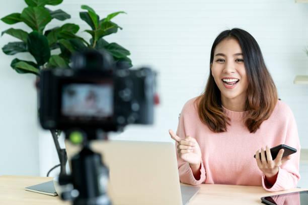 junge attraktive asiatin blogger oder einen blick in die kamera und sprechen auf video-aufnahmen mit technologie. social media influencer personen oder inhalte maker konzept in entspannen lässigen stil zu hause. - fotohandy stock-fotos und bilder