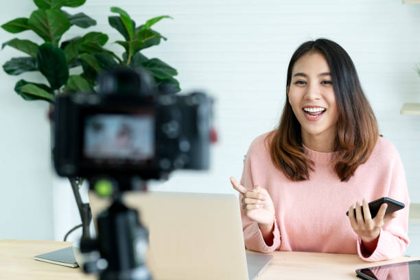 young attractive asian woman blogger or vlogger looking at camera and talking on video shooting with technology. social media influencer people or content maker concept in relax casual style at home. - interação com o cliente imagens e fotografias de stock