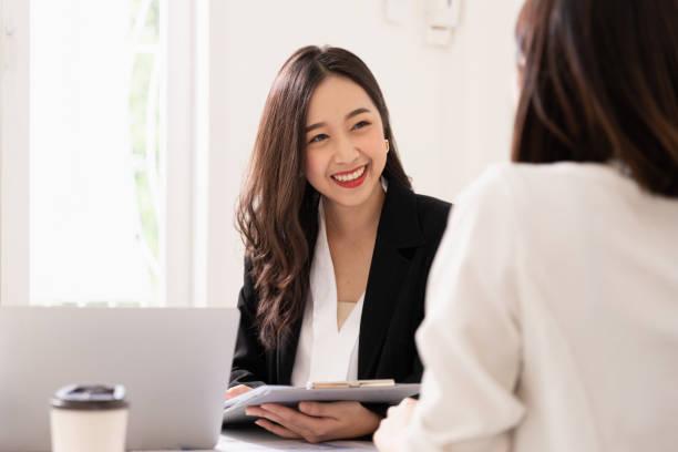 eine junge attraktive asiatische frau interviewt für einen job. ihre interviewer sind vielfältig. personalleiter führt vorstellungsgespräch mit bewerbern im amt - feedback stock-fotos und bilder