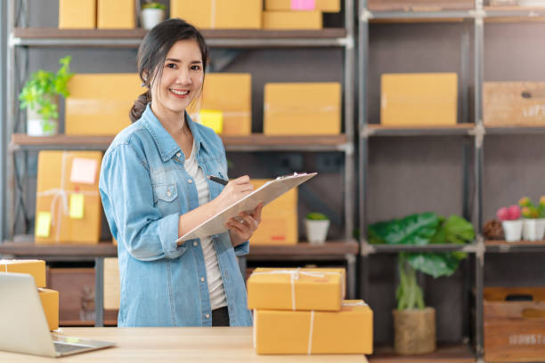 Young attractive asian woman owner startup business look at camera work happy with box at home prepare parcel delivery in sme supply chain, procurement, omnichannel or coronavirus quarantine concept. stock photo