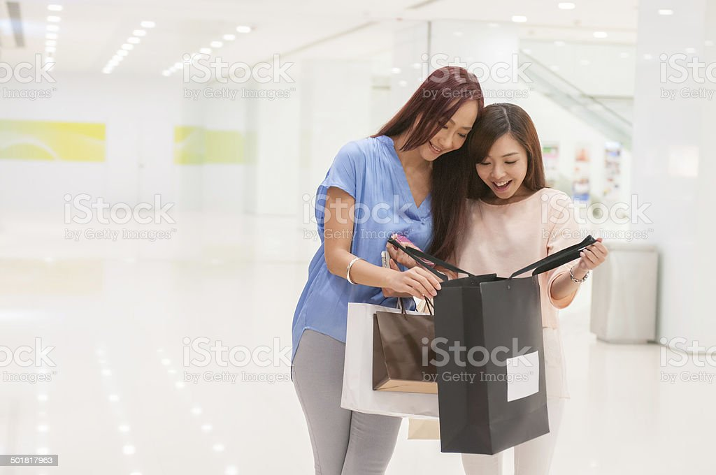 Young, Attractive Asian Women Looking at Purchases stock photo