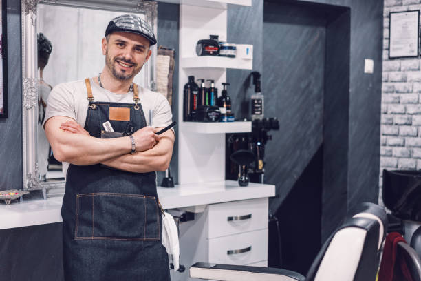 Young attractive barber at his barbershop stock photo