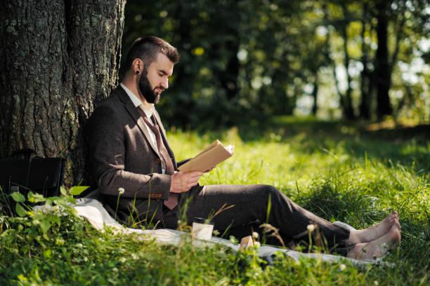 junge attraktive bärtige geschäftsmann sitzt auf grünem gras unter baum und ruht im park. lesen sie buch, trinken sie kaffee. entspannt, arbeitsmüde, mittagspause. - mensch isst gras stock-fotos und bilder