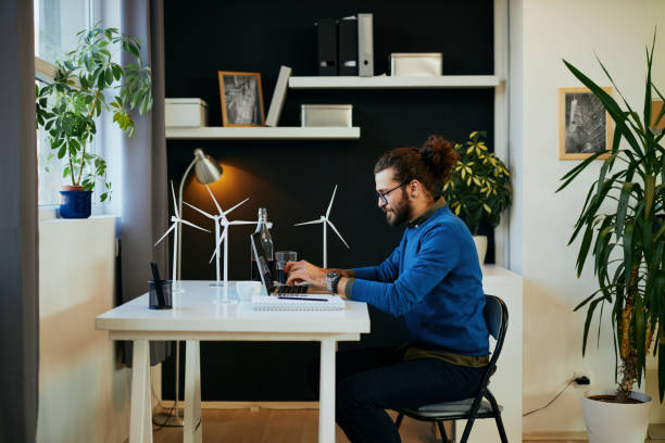 Young attractive bearded employee sitting in his modern office and using laptop for writing report about sustainability. stock photo