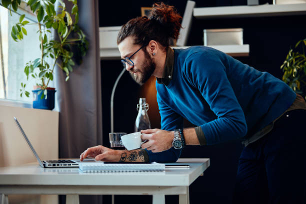 Young attractive bearded hipster with curly hair leaning on table, drinking coffee and surfing on internet while standing in home office. stock photo