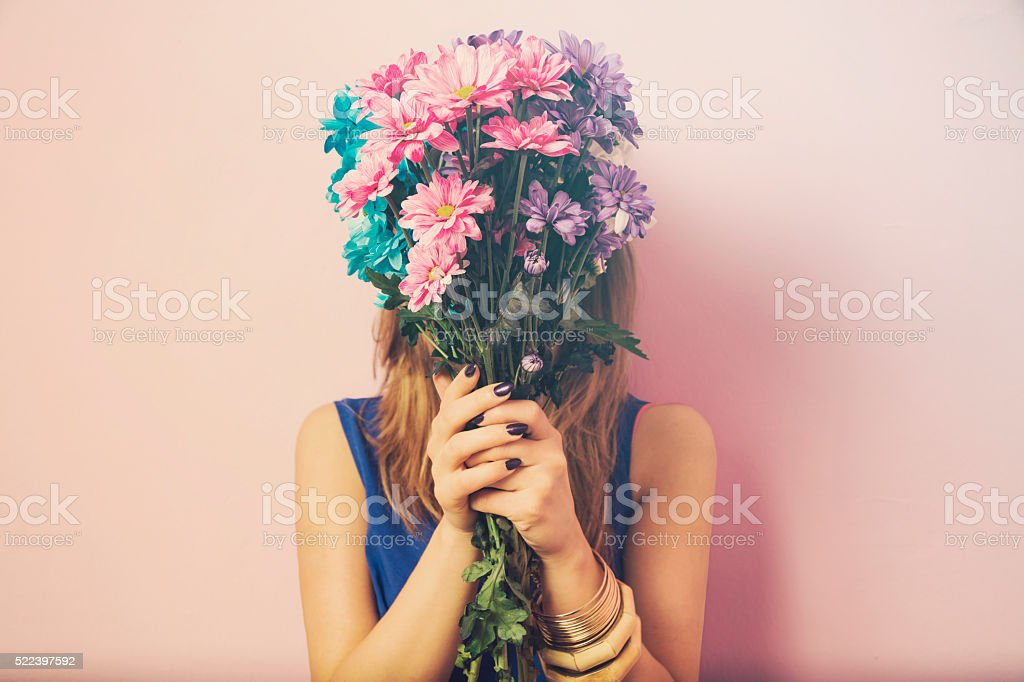 Young attractive beautiful woman smelling flowers. bildbanksfoto