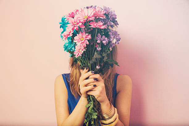 young attractive beautiful woman smelling flowers. - flowers stock photos and pictures