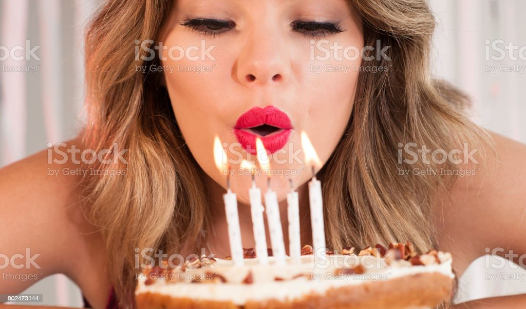 young attractive birthday girl blowing out candles on a cake stock photo