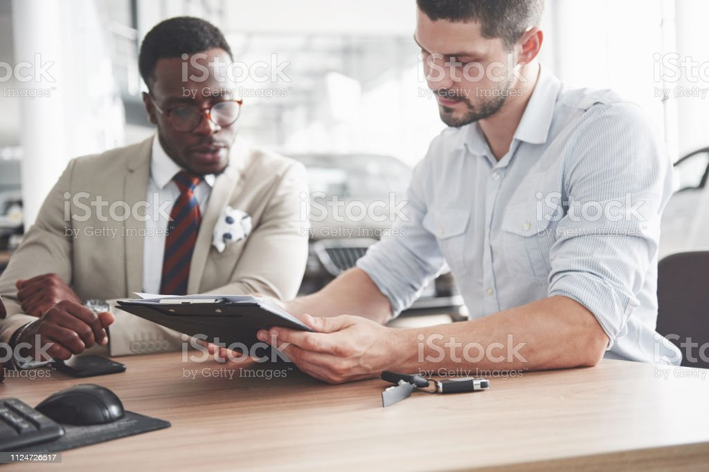 Ein junge attraktive schwarze Geschäftsmann kauft ein neues Auto, er unterschreibt einen Vertrag und nimmt den Schlüssel an dem manager – Foto